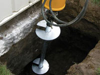 Installing a helical pier system in the earth around a foundation in Manchester